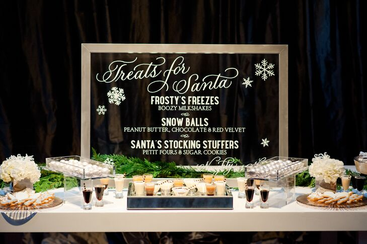 """Beneath a mirrored sign that read, """"treats for Santa"""" were winter-themed sweets such as spiked milkshakes, snowball-themed cake balls and stocking stuffers including gift-wrapped petits fours and snowflake-shaped sugar cookies."""