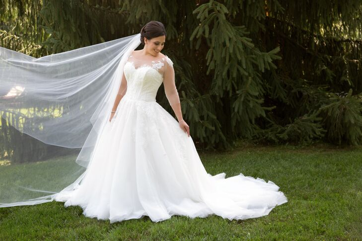 "Roxanne wore a ball gown by Rosa Clara Bridal, which featured an illusion neckline with lace appliques and tulle sleeves. "" I loved the idea of having sleeves because of how elegant and classy it looked,"" Roxanne says."