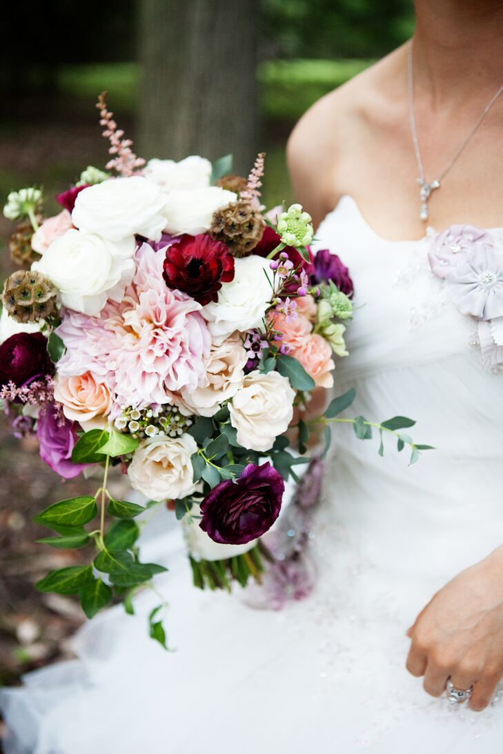 The bridal bouquet contained peach roses, lavender roses, purple wax flowers, light pink astilbes, scabiosa pods, light pink dahlias, and greenery, as well as white, burgundy and peach ranunculus.
