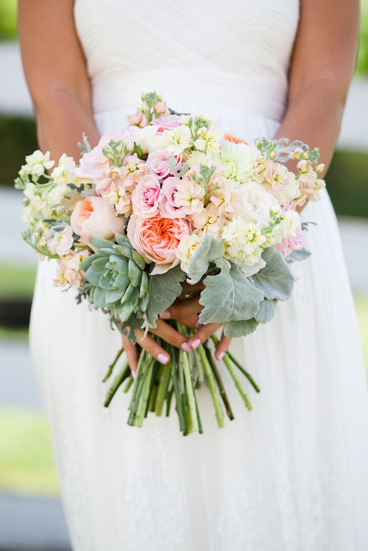 Pastel-colored roses and natural succulents filled this romantic bouquet created by Wallflower Designs. For a more simple look, each bridesmaid carried a white bouquet of baby's breath.