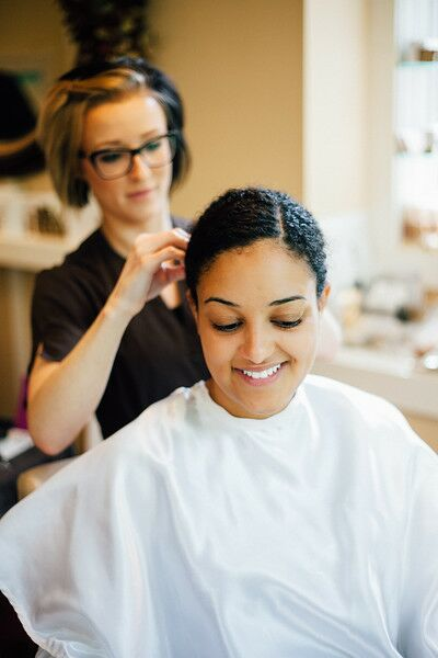 "Kelsey didn't want to risk her super-curly hair having a mind of its own on her wedding day, so the stylist pulled it back into a low bun, parted on the left side. Not a big makeup person, Kelsey kept her makeup simple and natural, ""like a better version of my everyday self,"" she says."