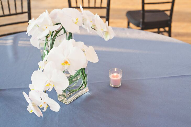 An elegant arrangement of white lush orchids were placed in a square glass vase on blue covered dining tables.