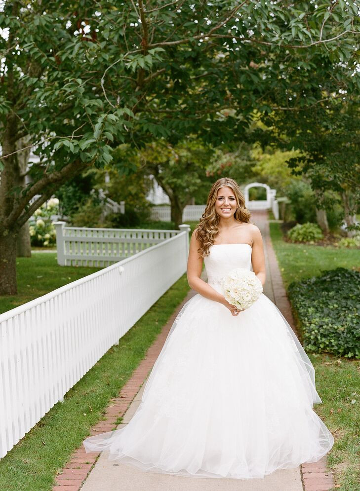 """When it came to her wedding day style, Caity kept things classic to suit the wedding's timeless feel. She had always dreamed of walking down the aisle in a Vera Wang gown, so when it came to finding her dress, she took her mother, mother-in-law, cousin and best friend with her to the designer's Boston boutique. She settled on a striking ball gown with a strapless, lace bodice and airy organza overlay with delicate lace appliques. She added a crystal belt to give the dress a hint of shimmer and wore a matching Vera Wang veil for the ceremony. """"I always wear my hair down and knew I wanted it to wear it down for our wedding,"""" says Caity. """"I wanted to look like myself, but a better version!"""""""