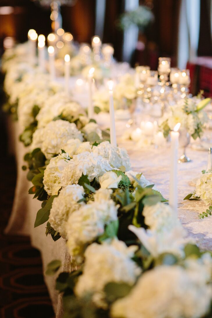 Vintage silver candelabras, textured linens and luscious white blossom garlands decorated the banquet table at the reception at Julia Morgan Ballroom in San Francisco, California.