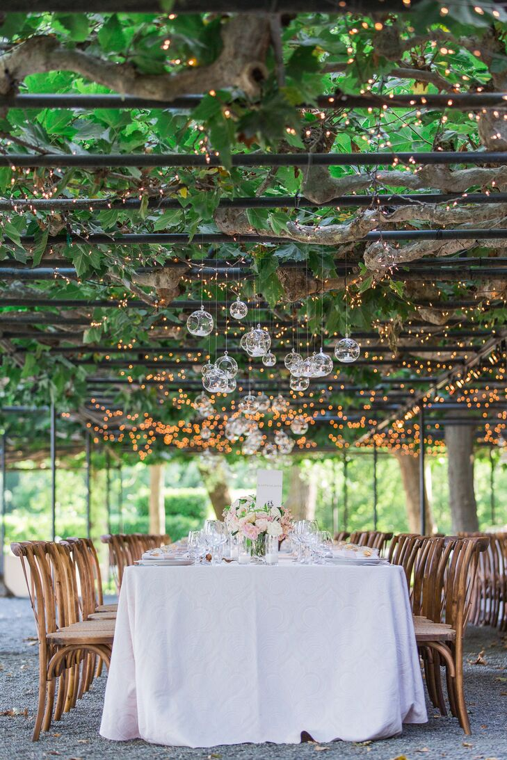 "Tables sat under a shady arbor in the garden, decorated with vases of peach and pink blossoms. ""The bubble vases hanging overhead at dinner were my favorite part of the reception decor,"" Kristina says. ""We had over 160 of them hanging in the arbor of the reception."""