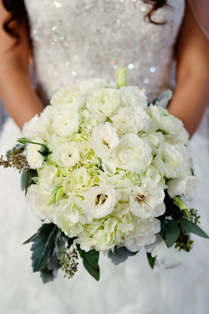 Miriam paired her eye-catching beaded and ruffled wedding dress with a classic all-white bouquet of white ranunculus, lisuanthus and hydrangeas, with greenery, dusty miller and seeded eucalyptus. To go with the rustic theme, it was wrapped in burlap.