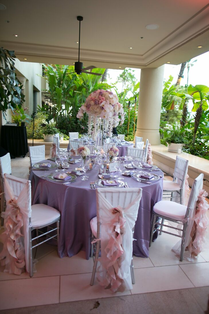 Purple tablecloths were set with silver place settings while silver Chiavari chairs were draped in cascading blush fabric at the reception.