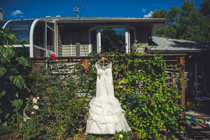 Aline wore a Paloma Blanca mermaid gown with a lace bodice and tiered skirt.