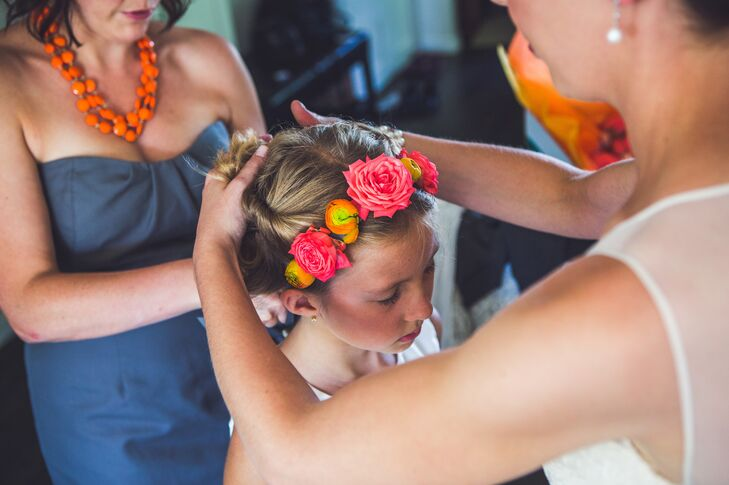 The flower girls wore a bright flower crown with orange ranunculuses and pink roses.