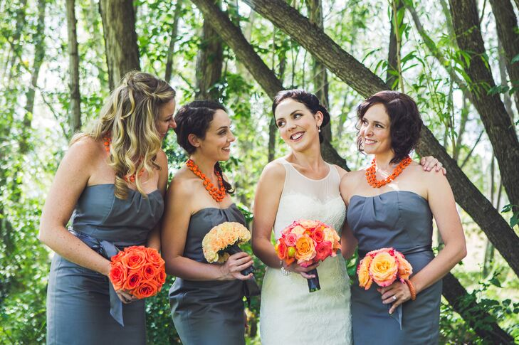 The bridesmaid's gray strapless dresses perfectly complemented the bright orange bouquets they carried.