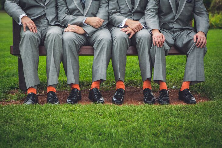 The groomsmen wore orange socks under their gray suits in keeping with the orange theme of the wedding.
