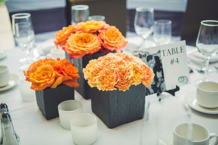 Orange roses and carnations were displayed in dark gray square boxes for the centerpiece decor.