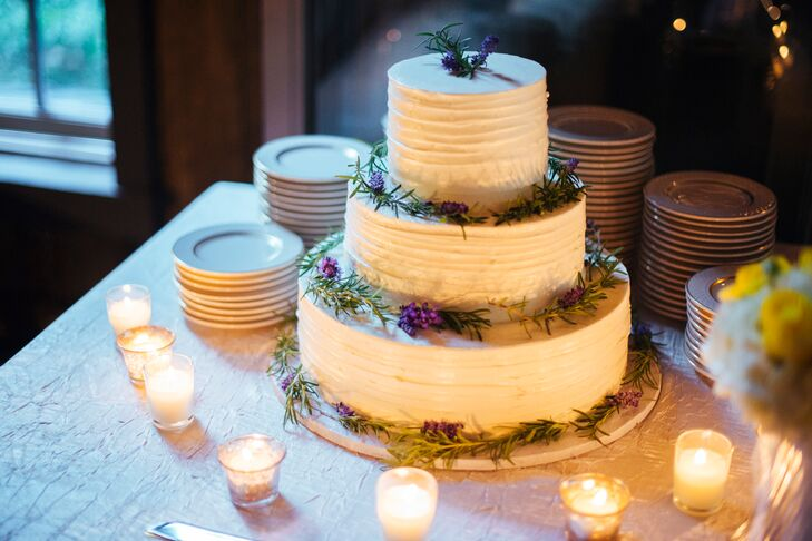 The three-tier white cake was decorated with fresh purple flowers and surrounded by small candle votives.
