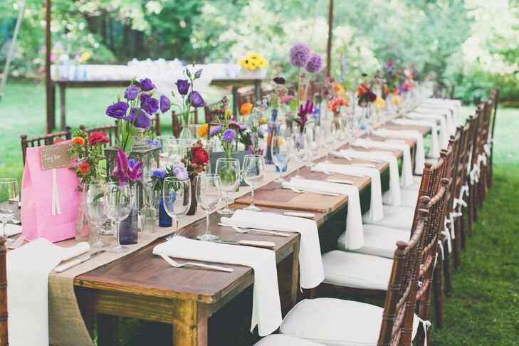 Three sections of long walnut farm tables were set up inside the reception tent around the dance floor. The tables were set with burlap table runners, and more than 200 vintage bud vases, and lanterns and votives.