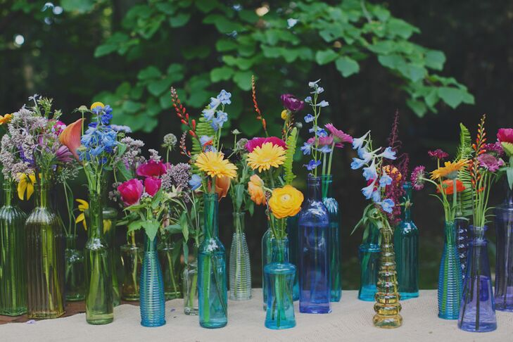 """Rebecca, from Rebecca Shepherd Floral Design, used all hot, vibrant wildflowers: reds, pinks, blues, violets, oranges, yellows. """"Bright, non-traditonal flowers made it feel like a celebration of love in an enchanted forest,"""" says Ariel."""