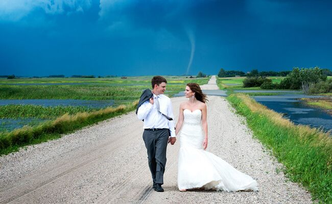 Newlywed couple walking in the country in front of a tornado.