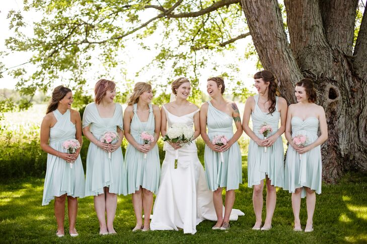 Bridget shared a happy moment with her bridesmaids, who stood around her wearing mint green dresses in a variety of styles.