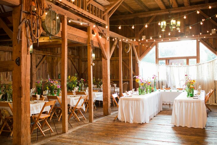 Inside the wooden barn, dining tables dressed in white tablecloths seated guests under elegant string lights. The barn interior had exposed wood everywhere, adding to the rustic vibe at the Barn & Gazebo in Salem, Ohio.