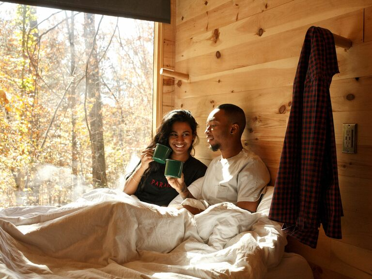 couple in Getaway cabin drinking out of mugs in bed