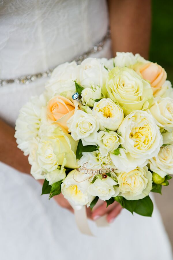 """Michelle held a gorgeous round bouquet filled with garden roses and spray roses in shades of peach and white. """"Inside my bouquet, we secured my 'something old,' a brooch from my nana (paternal grandmother), and my 'something blue,' which was a family ring from my husband's mother,"""" Michelle says. """"The bouquet base was wrapped with my 'something borrowed,' fabric from my mother's wedding dress."""""""