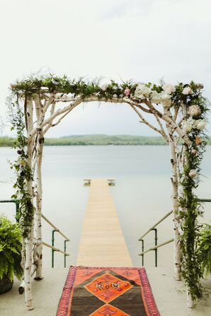 Waterfront Ceremony Space with Patterned Rug and Birchwood Arch
