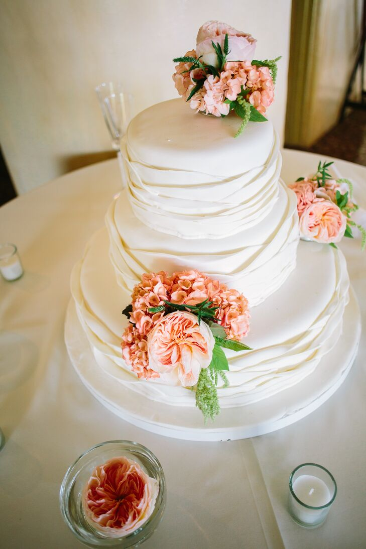 """""""Our wedding cake was a three-tiered marble cake finished with a ruffled, ivory buttercream frosting and garden roses on each level,"""" says Brittney. """"Our guests raved about our cake for days!"""""""