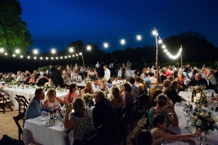 Wine barrels, vineyard wine crates, cafe lights and iron lanterns with green garlands created an atmosphere of natural, romantic Italian beauty in Austin, Texas.