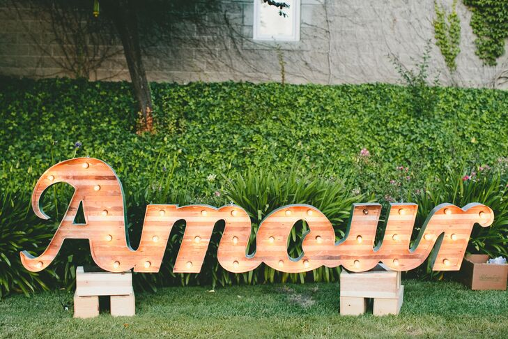 Wooden marquee lights spelling out the word amour cast a warm glow over the expansive vineyard lawn and added an element of playfulness to the decor.