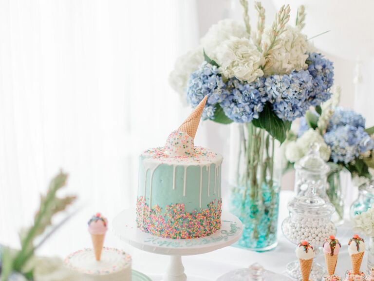 Light blue bridal shower cake with sprinkles and upside down ice cream cone on top