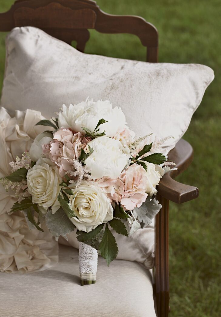"""Broad Brook Gardens added a romantic touch to Laura's wedding day look with a full bouquet of white and blush florals. Wrapped with white ribbon, the couple's florist designed an arrangement of white roses, pink hydrangea, pink lavender, white peonies and dusty miller. """"My favorite flowers are hydrangeas and peonies, so I wanted the majority of my arrangements to include them,"""" Laura says."""