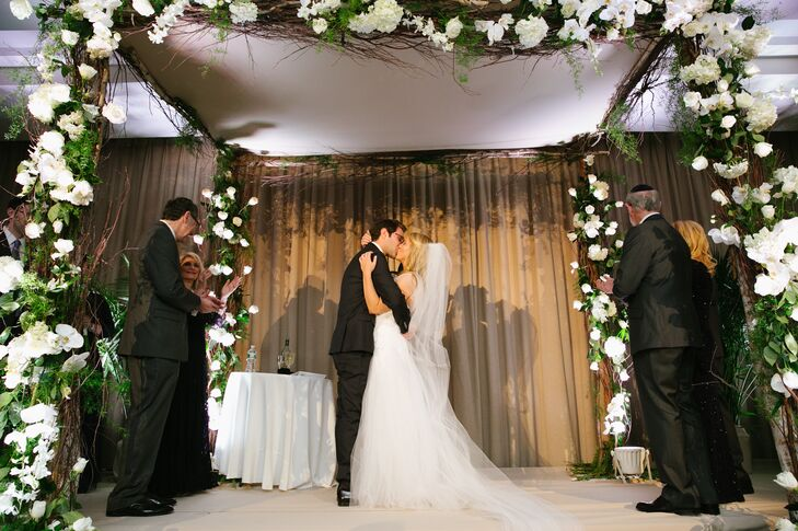 Lillian and Brian loved the natural-looking flower arrangements at their reception so much that they asked their florist to incorporate the same effect on their traditional orthodox wedding chuppah. The chuppah was covered with white flowers and lush greens, along with branches for an ethereal effect.