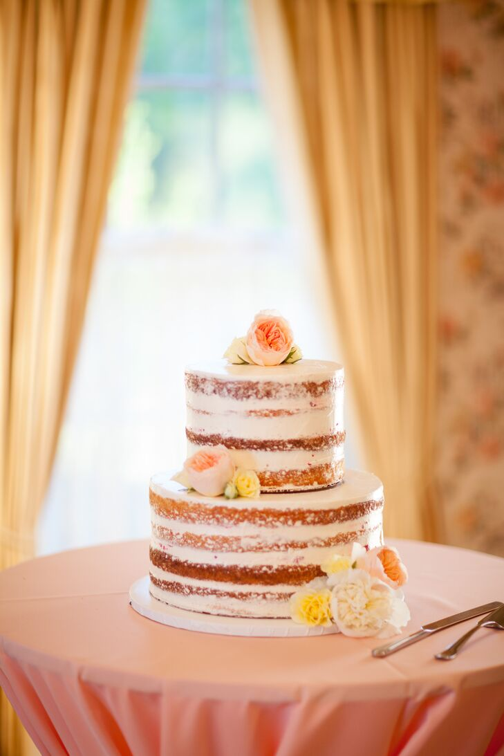 The bride and groom had a bright and simple theme so it was only fitting they have a bright and simple cake. The multi-tier unfrosted cake was lightly coated in powdered sugar and accented with light coral and yellow flowers.