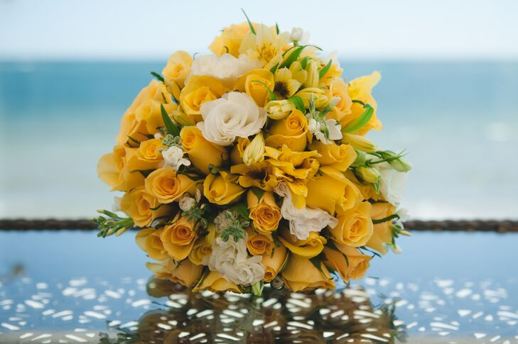 The bride's bouquet was composed of tropical flowers in white and yellow with accents of greenery throughout.