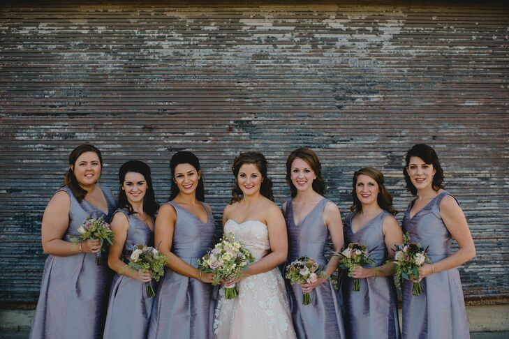 The bridesmaids wore these dupioni silk tea-length dresses in lavender. Each one had a V-neck and slight pleating along the hi-low skirt. Everything from their half-up, curled hairstyles to stud earrings and low, natural bouquets from Blooms matched to the T.