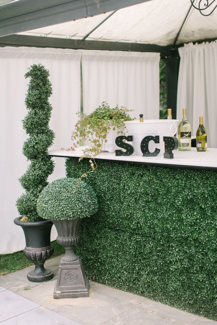 Bringing their English garden theme to life, the couple's three signature cocktails—manhattans, sidecars, and mint vodka lemonades—were served at a boxwood-trimmed bar framed by elegant cast-iron urns bearing sculptural boxwood plants.