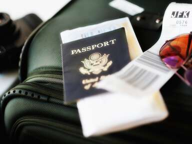 passport with luggage packed for travel