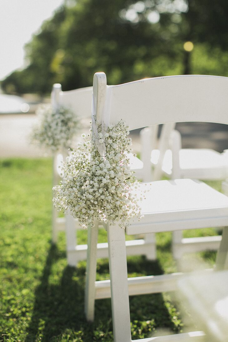 The chairs on the ceremony aisle were decorated with small bouquets of baby's breath.