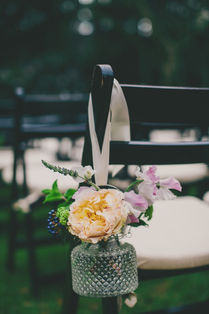 During the ceremony, the aisle was lined with glass jars of fresh flowers in lavender and peach tones. Each jar hung from the side of a guest's chair by a satin ribbon for a whimsical yet simple touch.