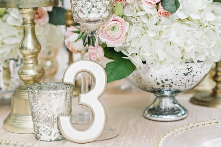 The freestanding table numbers were painted champagne and were propped up against the mercury glass and tall glass candleholders.