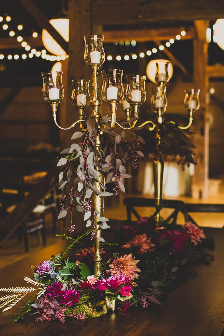 The head table at the reception had centerpieces assorted with pink and red flowers around two large candelabras, accented with fern and moss.