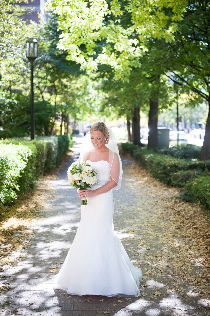 Marguerite wore a strapless, trumpet-fit wedding dress with lace overlay and an elbow-length veil. She accented the dress with a silver sash that matched her groom's silver tie.