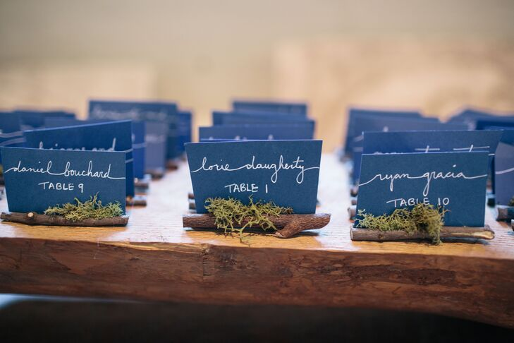 The groom's family helped to create a log escort card holder made from sticks and moss.