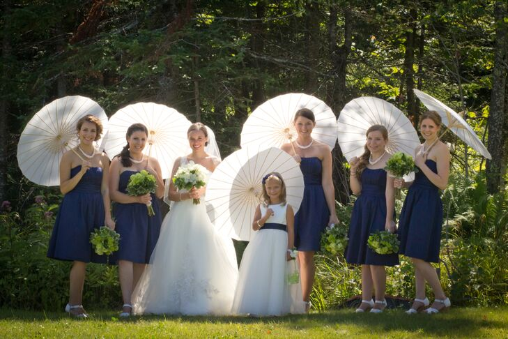 The bridesmaids wore navy cocktail length strapless dresses paired with Toms wedges. The white paper parasols they carried added a romantic touch to their look.