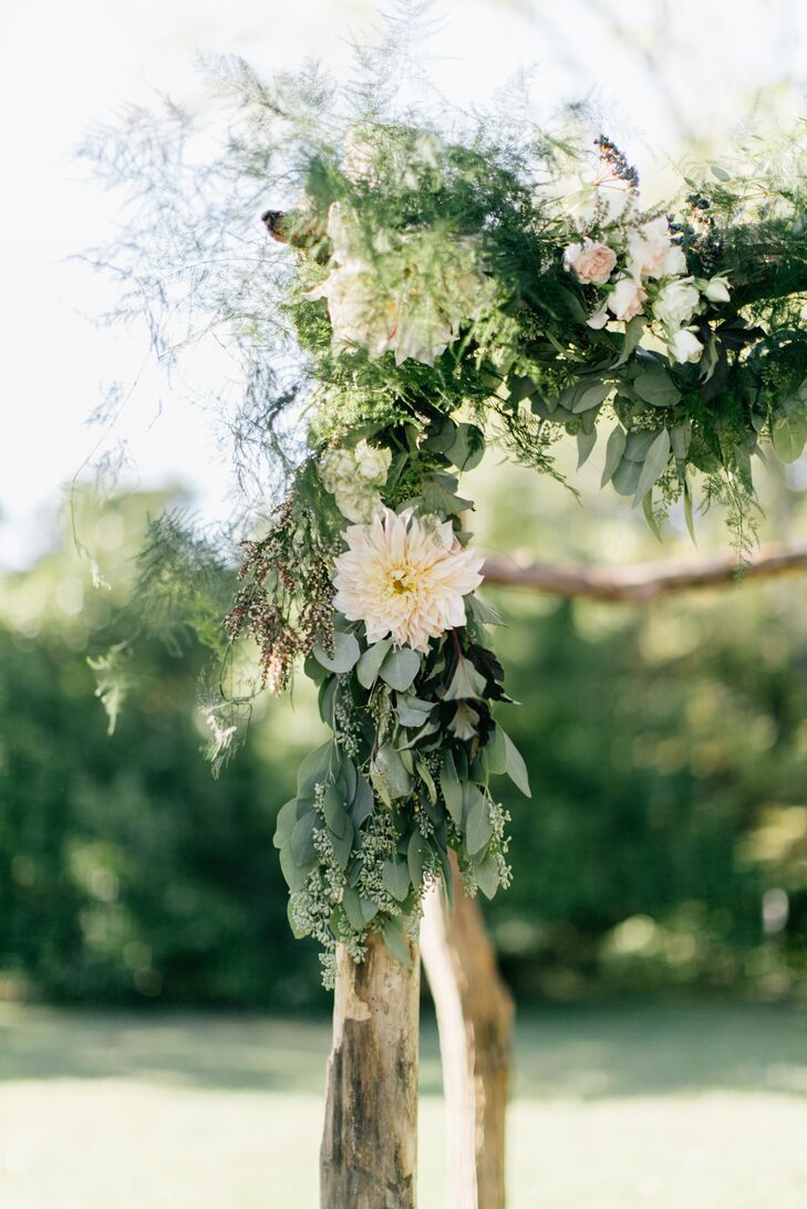 "The birchwood arch under which the couple were married was adorned with eucalyptus, rose, dahlia and greenery, inspired by Heather's experience in Amsterdam, the Netherlands, where she lived for two years. ""Floral arrangements in the Netherlands are often very textured and I wanted to bring that aesthetic to the wedding,"" she says."