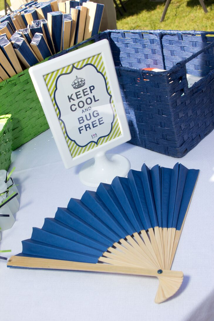 """Blue paper fans were displayed in green and blue baskets at the outdoor ceremony with a small sign that said """"Keep Cool and Bug Free."""""""