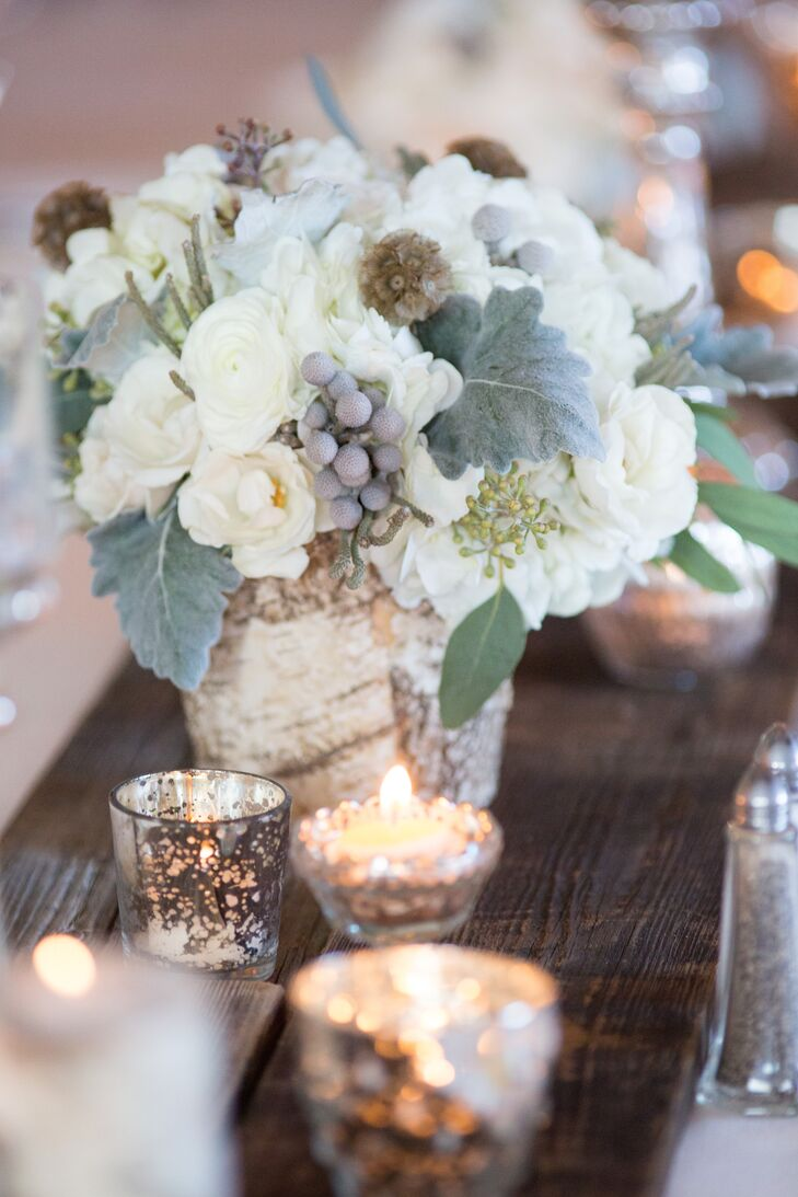 The rustic centerpieces included ranunculus, dusty miller, silver brunia balls, scabiosa pods and seeded eucalyptus.