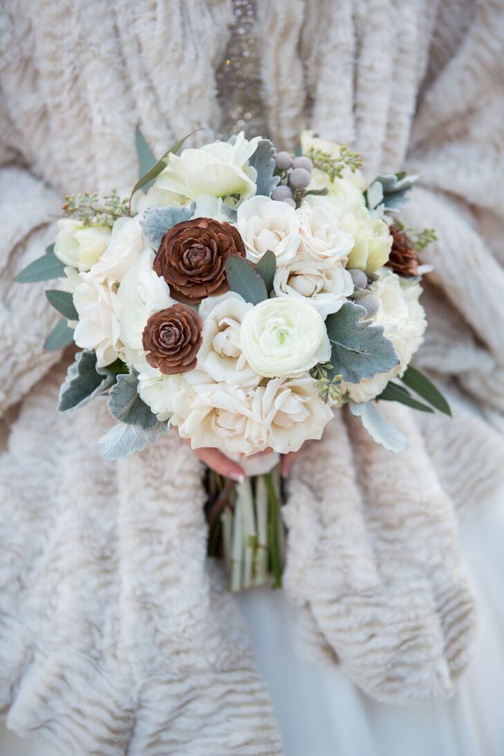 Jennifer carried white roses, ranunculus, dusty miller, pine cones, seeded eucalyptus and silver brunia balls in her wintery bouquet.
