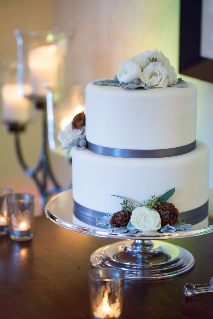 Jennifer and Scott enjoyed a two-tier white fondant cake decorated with gray satin ribbon, white ranunculus, seeded eucalyptus and pine cones made by the Four Season.