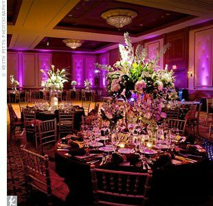 On the tables, a variety of white flowers, including calla lilies, lilies, roses, hydrangeas, delphiniums, and dendrobium orchids, picked up shades of magenta from the elegant lighting in the reception hall.