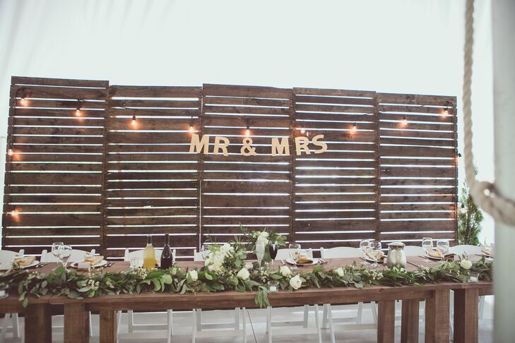 """Behind the king's table, a backdrop was made by the groom and his dad from wooden pallets that they broke down and stained. The backdrop was decorated with romantic string lights and a """"Mr. and Mrs."""" sign."""